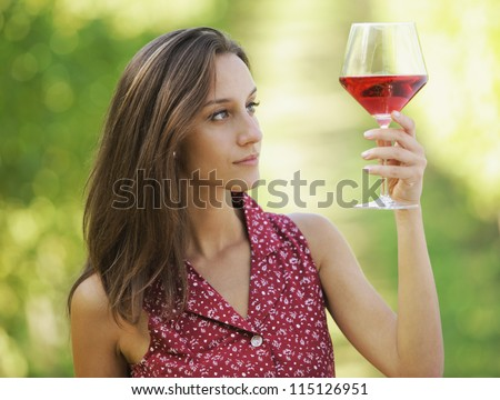 Vintner woman check red wine in a vineyard