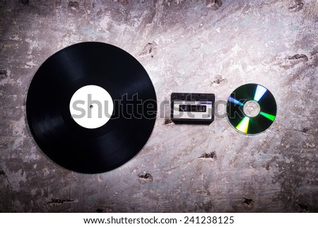 vinyl, cassette tape and CD on a concrete background illuminated lamps - stock photo