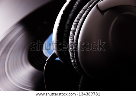 Vinyl disc with headphones close-up - stock photo