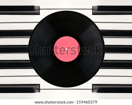 Vinyl phonograph record against piano keys - stock photo
