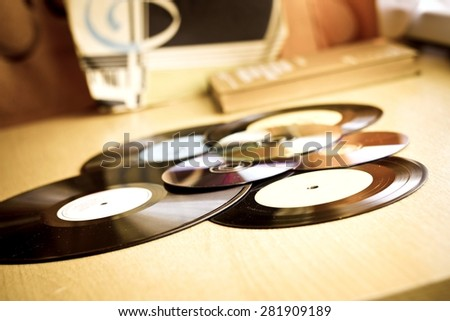 Vinyl record discs, CD and book on wooden table. Image with vintage filter - stock photo