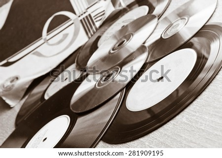 Vinyl record discs, CD on wooden table. Black and white image - stock photo