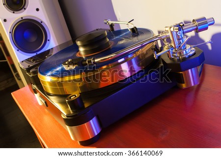 Vinyl record played on a hi-end turntable record player standing on red wood stand with speakers on background  - stock photo