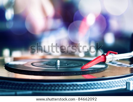 Vinyl record spinning on DJ player - stock photo
