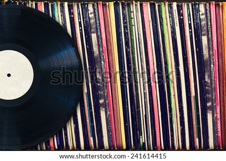 Vinyl record with copy space in front of a collection of albums (dummy titles), vintage process - stock photo