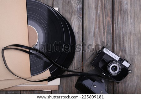 Vinyl records and paper covers and camera on wooden background - stock photo