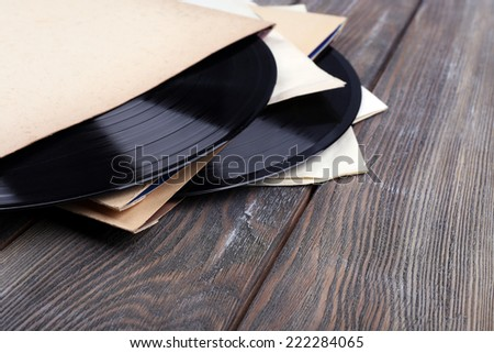 Vinyl records records and paper covers on wooden background - stock photo