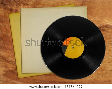 Vinyl records with cover on wooden table - stock photo