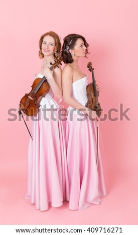viola and violin duo on a pink background - stock photo