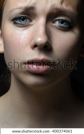 Violence and abuse of girls theme: portrait of a beautiful young girl with tears in her eyes, a sad woman in the studio - stock photo