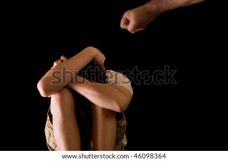 Violent child abuse - father's fist aims at teen son - stock photo
