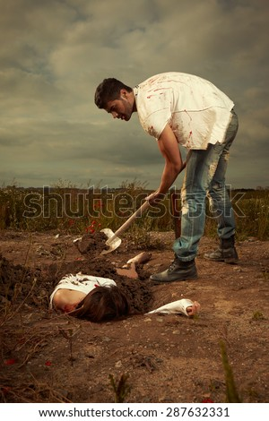 Violent criminal burying his victim - stock photo