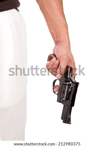Violent man holds a 357 magnum revolver at his side with his finger on the trigger. - stock photo