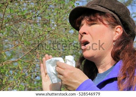 Violent sneezing with hayfever. A woman has hay fever
