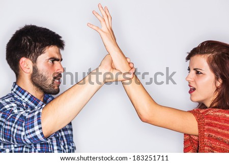 Violent young man causing pain to his scared wife - isolated on grey - stock photo