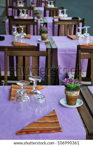 Violet and orange table setting in outdoor restaurant, Milan, Italy - stock photo