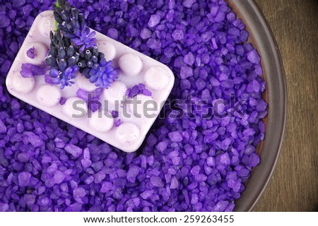 Violet bath salt and soap in dish on wooden background. - stock photo
