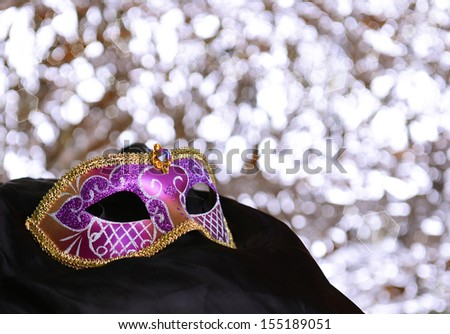 Violet carnival mask on black silk over silver bokeh background - stock photo