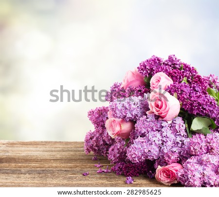 Violet Lilac flowers with pink roses close up on wooden table, copy space on gray bokeh background - stock photo
