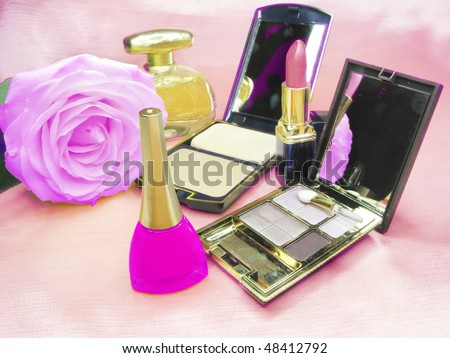 violet lipstick powder pink rose eye-shadows and perfume on satin cloth background