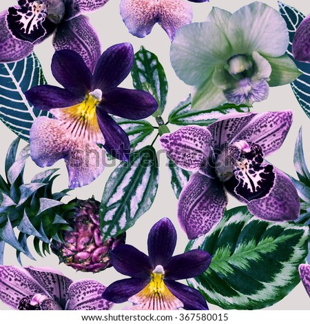 Violet orchid flowers with exotic leaves on the gray background. Tropical pattern in violet, purple and gray colors. Photo collage with exotic plants. - stock photo