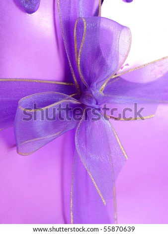 Violet ribbon bow on a pink gift bag - stock photo