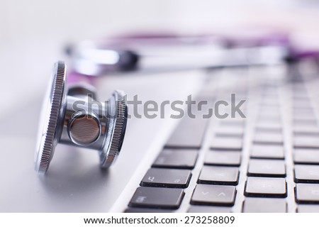 Violet stethoscope on a laptop computer - stock photo
