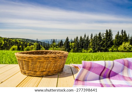 Violet tablecloth and wicker basket on wooden table - stock photo