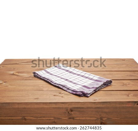 Violet tablecloth or towel over the surface of a brown wooden table, composition isolated over the white background