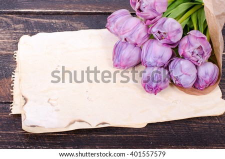 Violet tulips and vintage paper on a wooden background. Free space for your text.