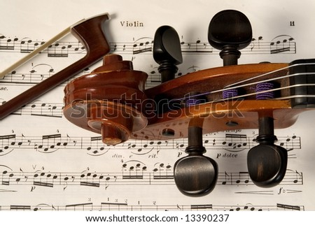 Violin and bow on music chart sheet - stock photo