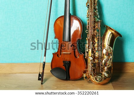 Violin and saxophone on the floor against blue background