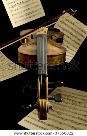 violin, bow and notation sheets by Mozart and Beethoven floating in front of black background - stock photo