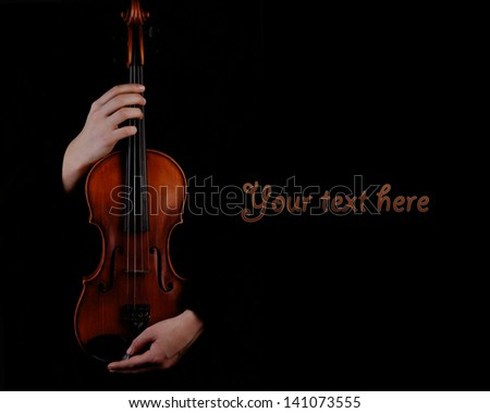 Violin in hands on black background - stock photo