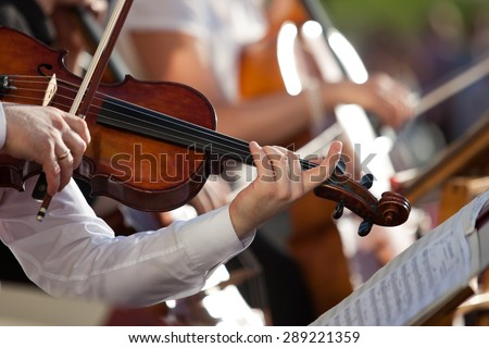 Violin in the hands of a musician in the orchestra closeup - stock photo