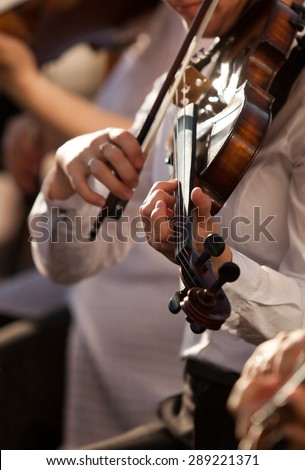 Violin in the hands of a musician in the orchestra closeup