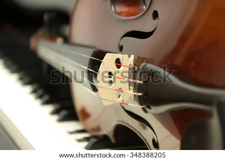 Violin laying on the side on the grand piano keyboard - stock photo