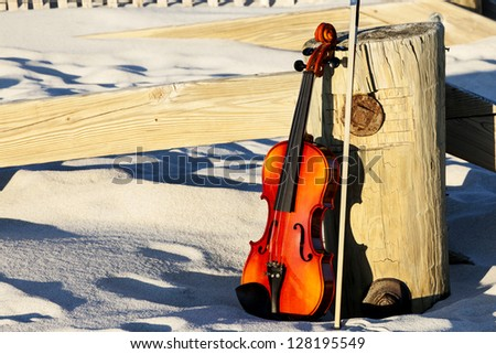 Violin leaning on a post in the sand. Long Island, New York. - stock photo