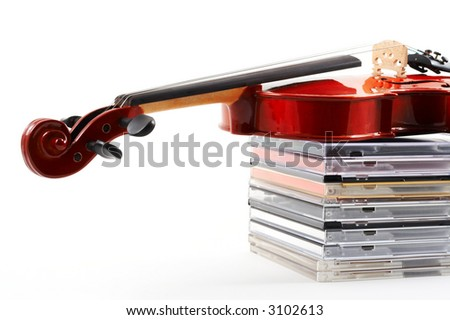 Violin lying down on stack of compact discs on white background, top angle view, horizontal, landscape orientation. Depicts a career in classical music. Commercialization of classical music.