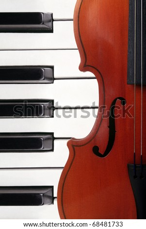 Violin lying on the piano - stock photo
