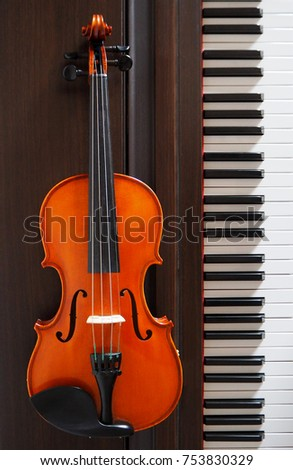 Violin next to a piano keyboard
