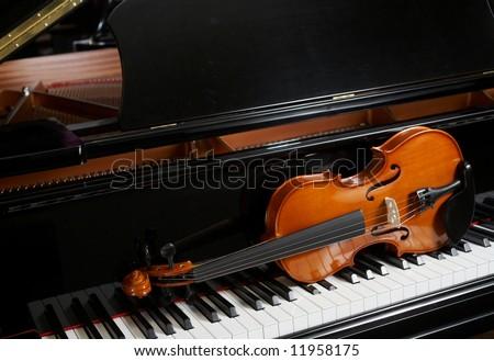 Violin on grand piano - stock photo