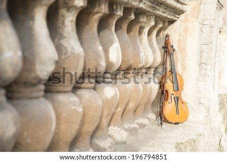 violin on old retro fence background in perspective Beautiful  music instrument standing near cracked wall backdrop Copy space for inscription - stock photo