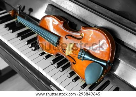 Violin on piano keys, closeup - stock photo