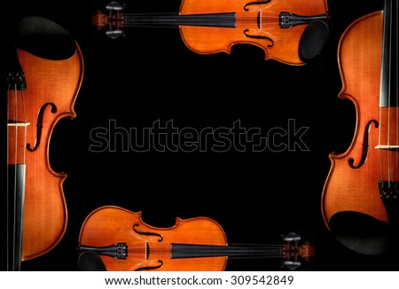Violin orchestra musical instruments on black background - stock photo