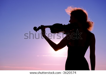 violin player performing solo at sunset - stock photo