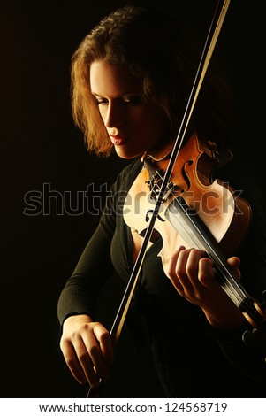 Violin playing violinist musician. Woman classical musical instrument player on black - stock photo