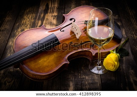 Violin, wine and yellow rose on dark wooden background - stock photo