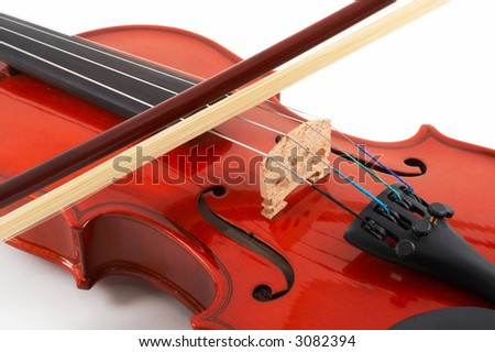 Violin with bow across strings on white background, top, angled view, closeup - stock photo