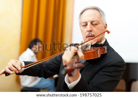 Violinist and pianist playing together - stock photo